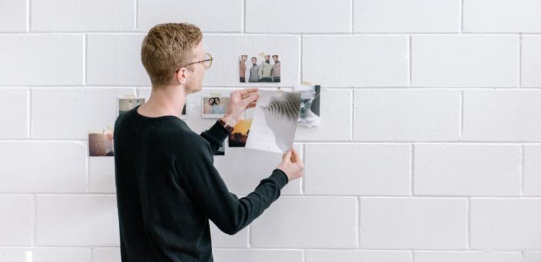 Man putting photos on wall